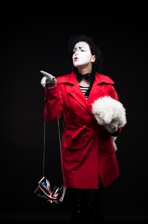 funny woman mime holding small fluffy dog and showing emotions photo