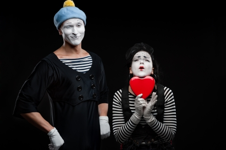 two funny mimes holding red heart isolated on black background Stock Photo