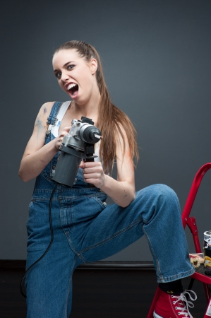 young funny woman standing at ladder and holding puncher photo