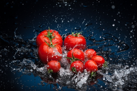 small group of fresh tomatoes lying over water splashes