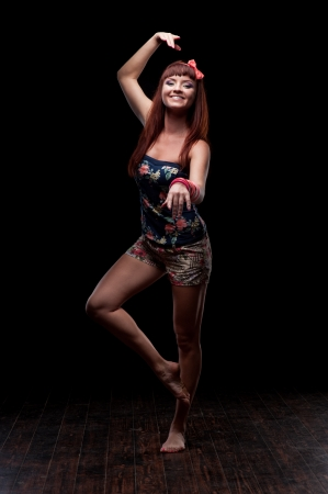 young caucasian red-haired female dancer showing move over black background Stock Photo - 21512312