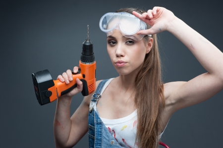 young sexy woman sitting at ladder and holding drill photo