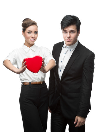 young smiling caucasian business couple holding red heart isolated on white background photo