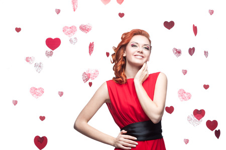 young smiling red-haired caucasian woman in red dress stay over red hearts  photo