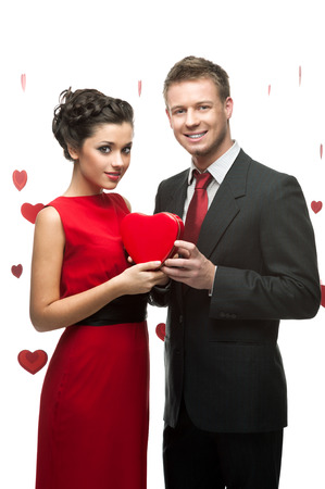 young smiling caucasian couple holding red heart isolated on white background photo
