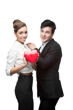 cheerful young caucasian business couple holding red heart isolated on white photo