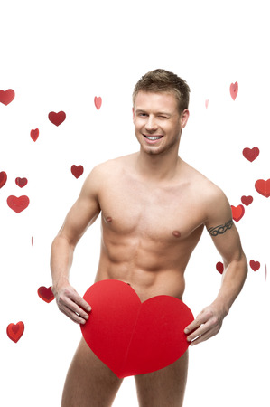 young cheerful caucasian funny naked man holding big red paper heart isolated on white background with falling red hearts photo