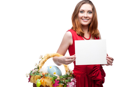 cheerful young woman in red dress holding easter basket and sign isolated on white