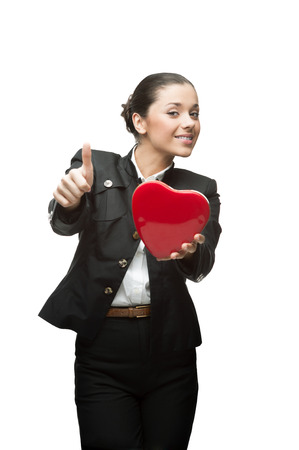 smiling young caucasian business woman in black suit holding red heart isolated on white photo