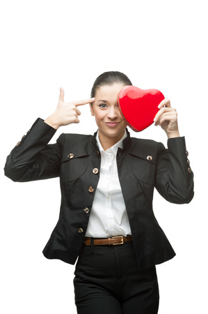 young cheerful caucasian brunette businesswoman in black suit holding red heart isolated on white photo