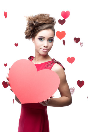 cheerful caucasian brunette young woman in red dress holding big red paper heart photo