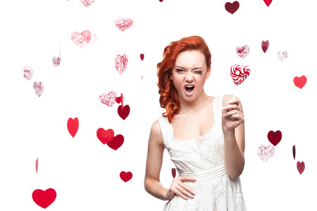 cheerful caucasian red-haired winking young woman holding lollipop. isolated on white photo