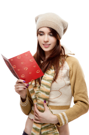casual caucasian happy young woman reading red postcard. isolated on white photo