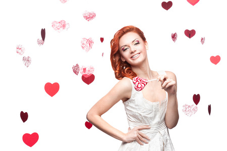 cheerful caucasian red-haired young woman holding lollipop. isolated on white photo