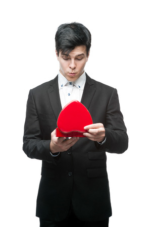 caucasian surprised young businessman holding red heart. isolated on white photo