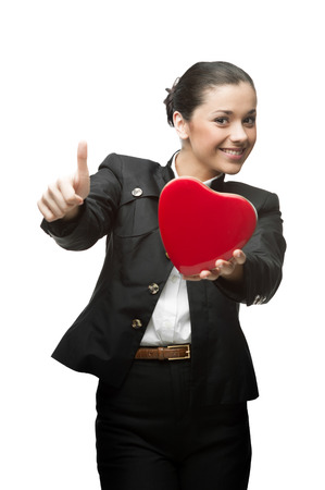 caucasian young happy smiling business woman holding red heart and showing thumbs up. isolated on white photo