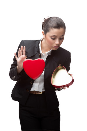 caucasian young happy business woman looking at empty red heart. isolated on white photo