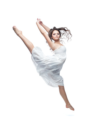 beautiful caucasian brunette woman in white dress dancing isolated on white background photo