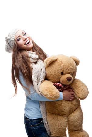 caucasian casual smiling young woman in winter clothing holding big soft Teddy Bear. isolated on white