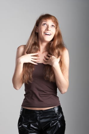 cheerful happy casual caucasian girl with long brown hair on gray background photo