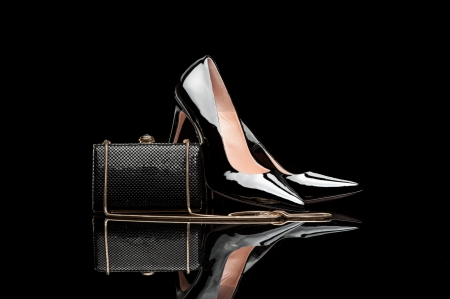 high heel shoes: composition of black female high heel shoes and clutch isolated on black Stock Photo