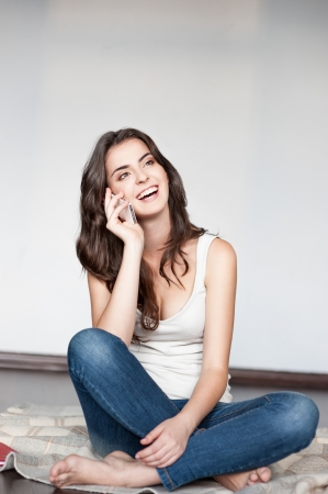 white singlet: casual brunette young woman in white singlet and jeans sitting on wool plaid and talking on cell phone Stock Photo