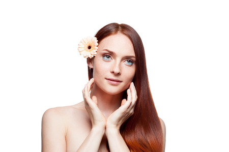 portrait of young caucasian red haired girl with flower in hair isolated on white photo