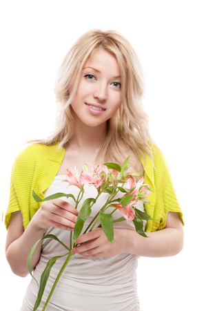 young casual caucasian blond woman smiling while holding flowers isolated on white photo