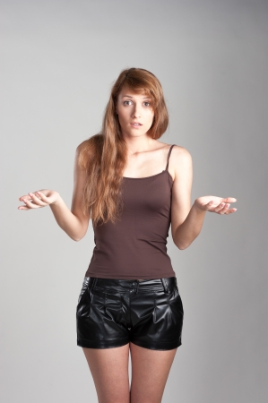 surprised casual caucasian girl with long brown hair on gray background photo