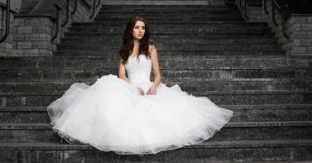 all'aperto ritratto di bella giovane donna bruna indoeuropea in abito bianco da sopra le scale di grigio su sfondo