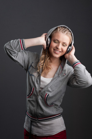 young cheerful casual caucasian woman with headphones over gray background photo