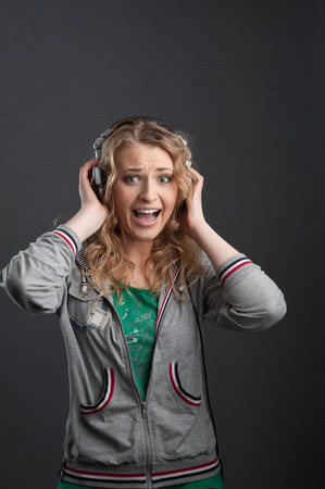 young cheerful screaming casual caucasian woman with headphones over gray background photo