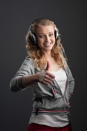 young cheerful casual caucasian woman with headphones showing thumbs up over gray background photo