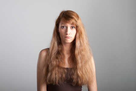 resentful casual caucasian girl with long brown hair on gray  photo