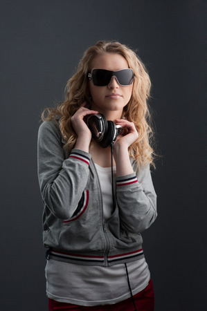 young cheerful casual caucasian woman with headphones in black sunglasses over gray background photo