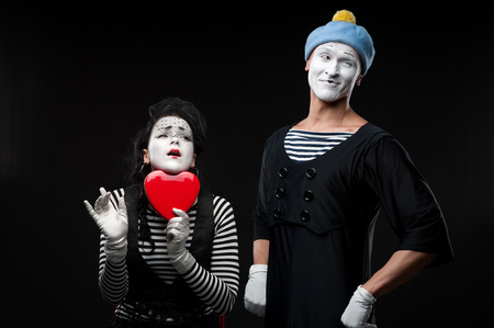 two funny mimes holding red heart isolated on black background photo