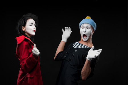 woman mime showing to male mime something to surprise him photo