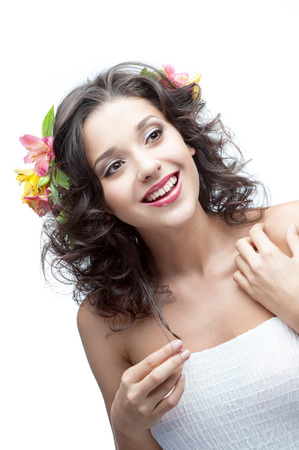 young attractive smiling caucasian woman with lily flowers in hair photo