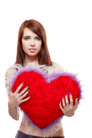 young smiling casual caucasian brunette woman holding red fur heart. isolated on white photo