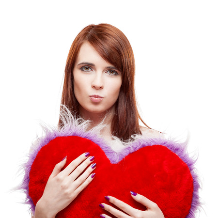 young cheerful casual caucasian brunette woman holding red fur heart. isolated on white photo