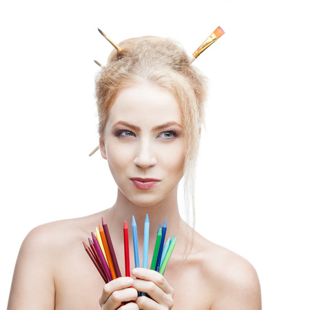 attractive young blond caucasian girl with brushes in hair holding color pencils while looking away with thoughtful expression photo