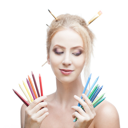smirking: young blond caucasian girl with brushes in hair holding color pencils while looking down with thoughtful expression and smirking