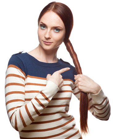 casual red haired young woman in striped  blouse holding and pointing at her hair isolated on white photo