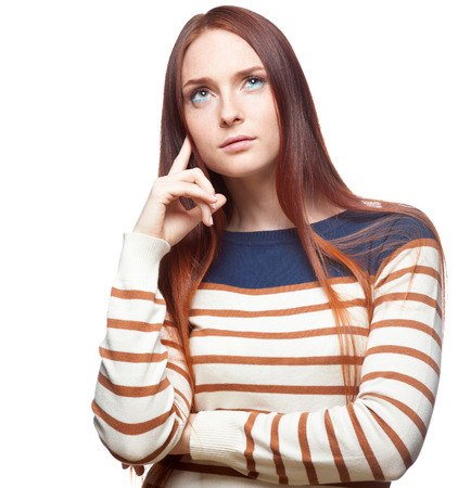 portrait of young thoughtful casual caucasian red haired girl in striped blouse isolated on white photo
