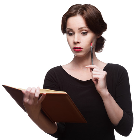 thoughtful business woman in black dress with diary photo