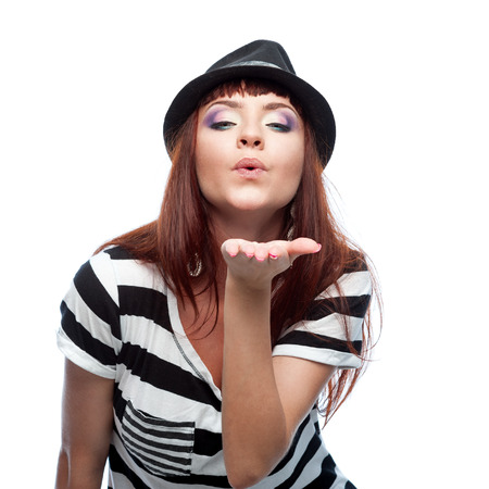 causasian: young stylish casual causasian brunette woman in hat and black and white stripe dress give a kiss. isolated on white