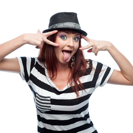 causasian: young stylish casual causasian brunette woman in hat and black and white short dress looking at camera with funny expression