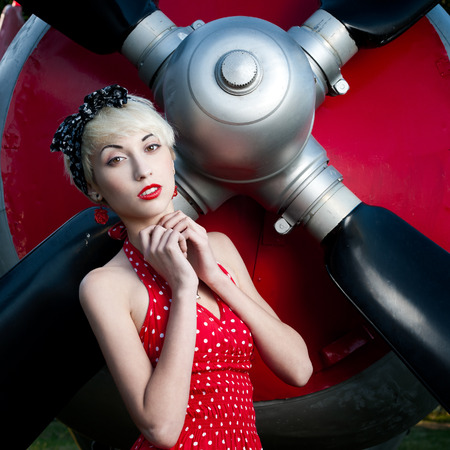 outdoors pin-up portrait of young blond sexy caucasian woman in red retro dress. photo