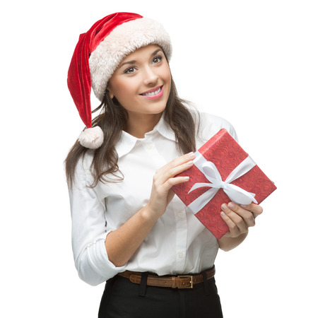 young cheerful caucasian brunette businesswoman in white blouse and santa hat holding christmas gift isolated on white photo
