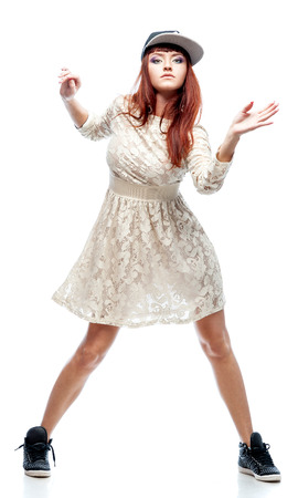 dancing girl: young caucasian red-haired female dancer showing move over white background